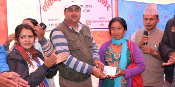 Bimala Nepali receiving citizenship certificate from Dhading's Chief District Officer, Umesh Kumar Dhakal. Photo by: Sarita Rai/Oxfam